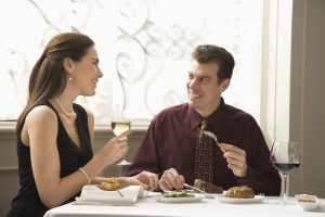 Mid adult Caucasian couple dining in restaurant and smiling.